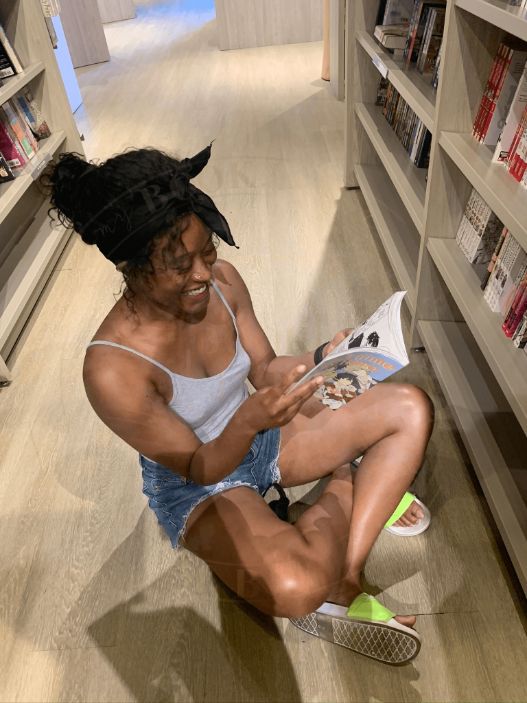 Image of Sash sitting on the floor wearing a grey tank top and blue jean shorts, smiling, reading in a bookstore