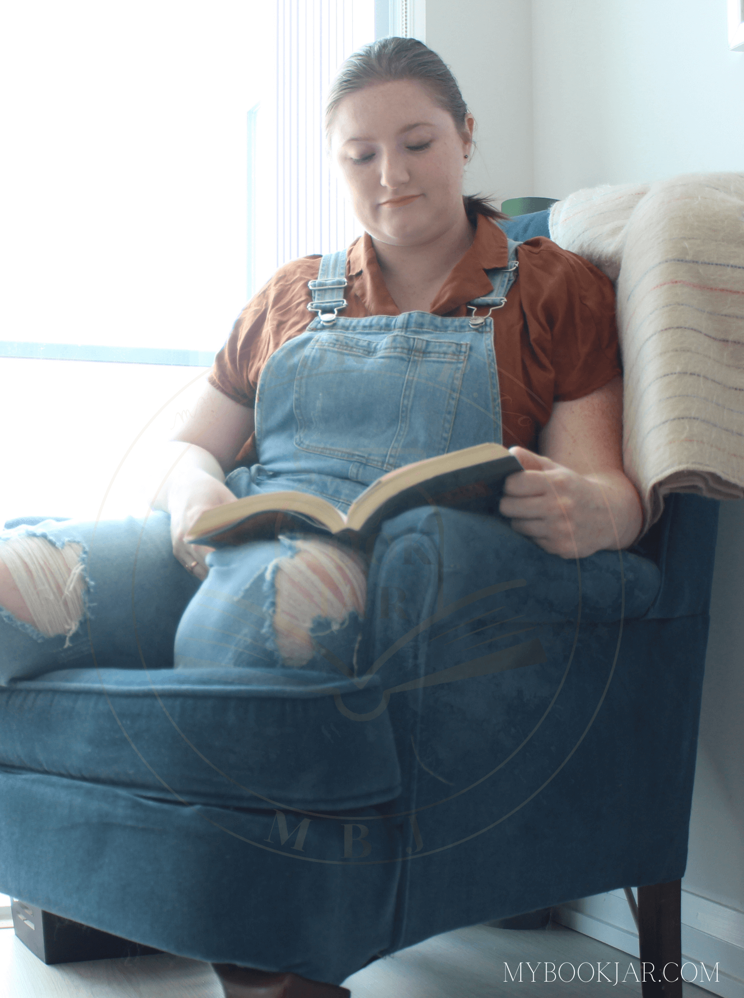 Favourite Places to Read image of Carmen in jean overalls and an orange collared shirt reading in her blue armchair before a window