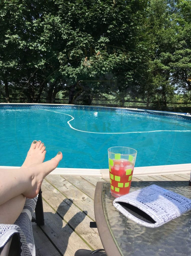 image of Carmen's perfectly manicured feet with a glass of red liquid and newspaper ipad sleeve on the right side with the pool in front.