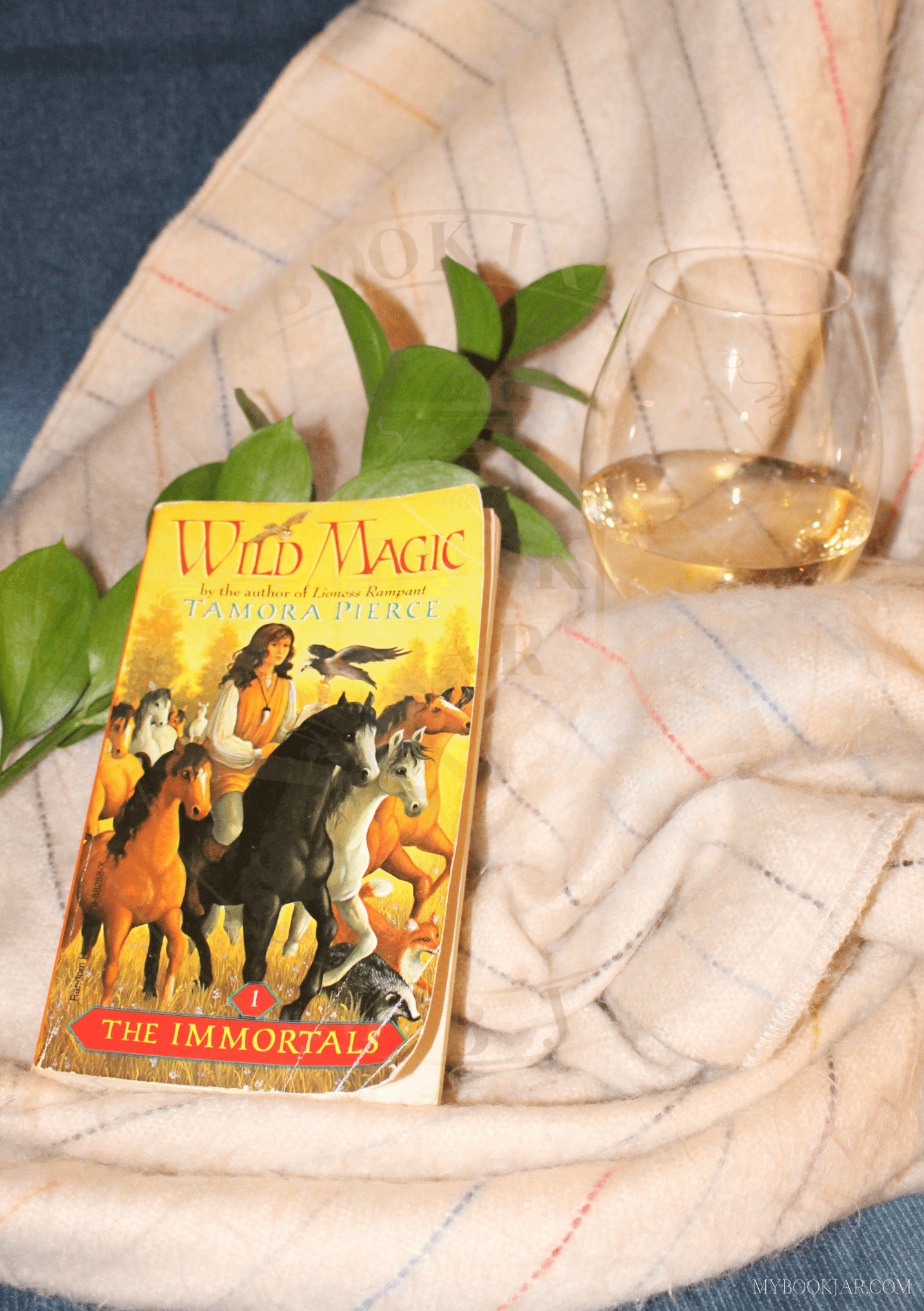 image of the book Wild Magic on a beige striped blanket with a glass of white wine and a piece of greenery.